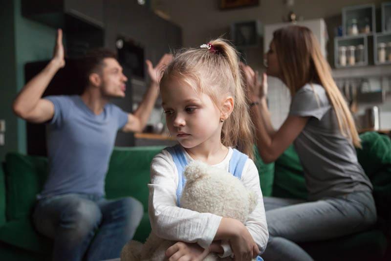 Eltern streiten sich, während trauriges kleines Mädchen ihren Teddybär umarmt