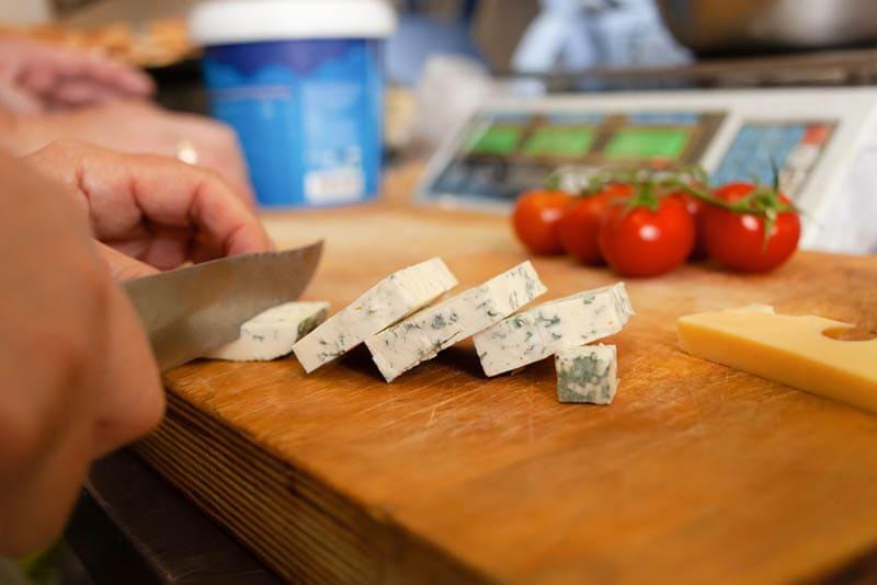 Frau schneidet Gorgonzola-Käse auf dem hölzernen Schneidebrett