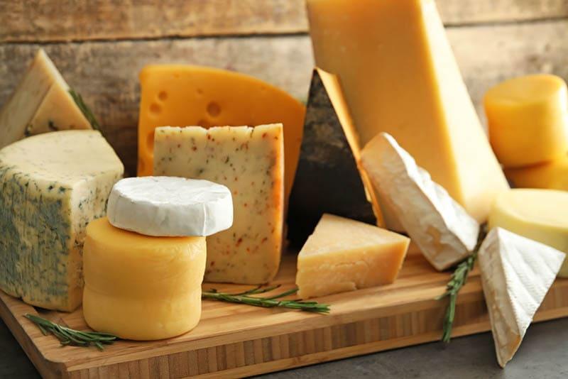 Holzbrett mit verschiedenen leckeren Käsesorten auf dem Tisch