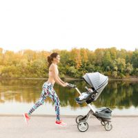 junge Mutter joggt mit Baby im Kinderwagen neben dem Fluss im Freien