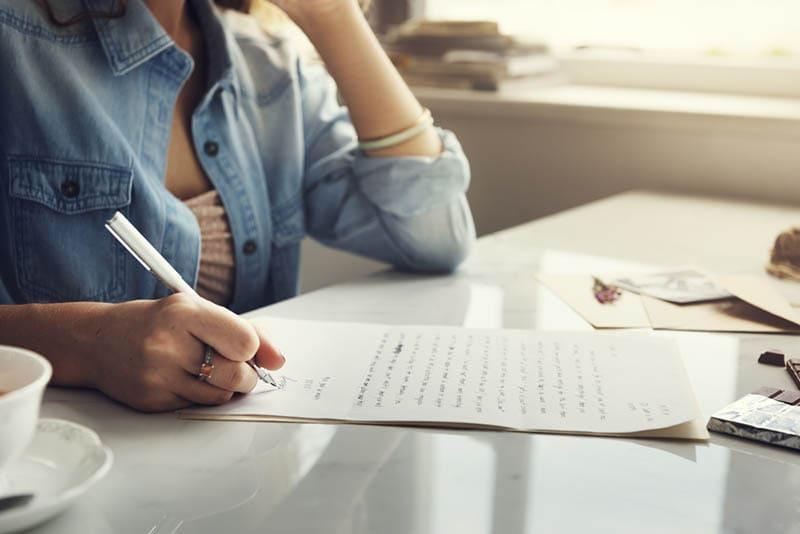 Junge Frau schreibt einen Brief am Tisch