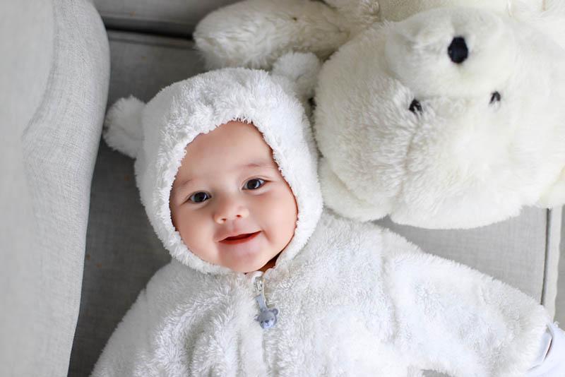 Kleinkind Baby Junge trägt Teddybär Kostüm liegt neben weißen Eisbären