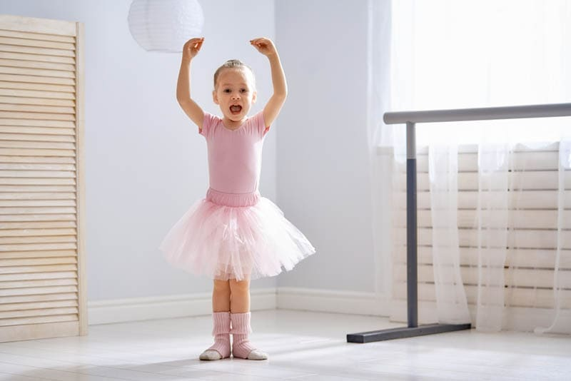 Mädchen in einem rosa Tutu tanzt in einem Raum als Ballerina