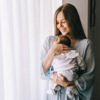 glückliche junge Mutter hält neugeborenes Baby am Fenster