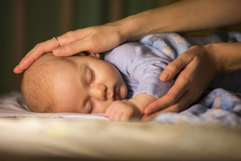Mutter streichelt ihr Baby, während es nachts im Bett schläft