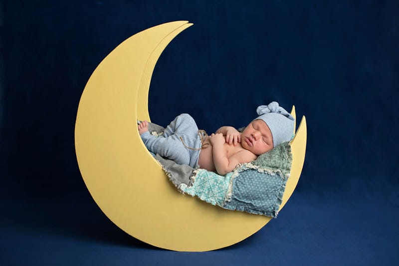 Neugeborenes Baby Junge trägt Pyjamahose und eine Schlafmütze auf Fotoshooting