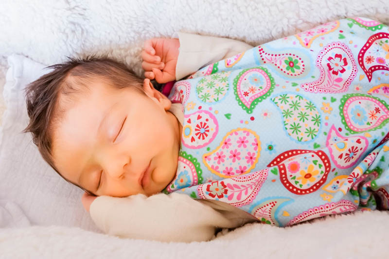 Neugeborenes Baby schläft in einem bunten Schlafsack im Kinderbett