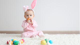 Baby trägt rosa Hasenohren und spielt mit Spielzeug