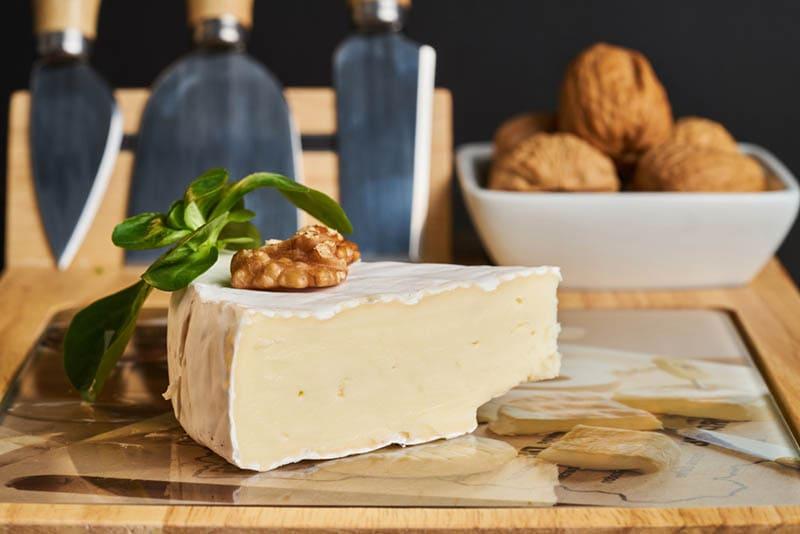 Scheibe leckerer Käse mit Walnuss auf dem Tisch