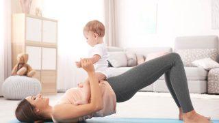 junge Mutter trainiert auf dem Boden mit ihrem Baby