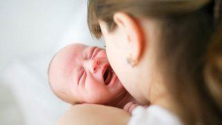 Junge Mutter, die versucht, ihr weinendes Neugeborenes zu stillen