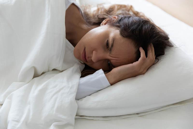besorgte Frau im Bett liegend auf dem Kissen mit weißer Decke bedeckt