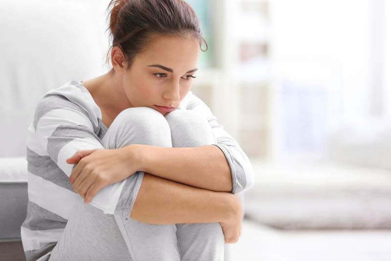 besorgte junge Frau sitzt in Gedanken auf der Couch