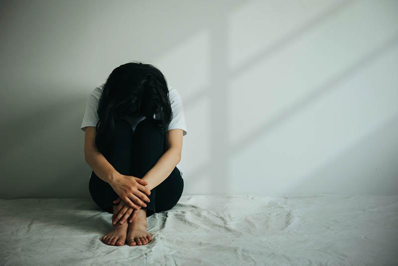 depressive Frau umarmt ihr Knie und weint, während in leeren Raum sitzen