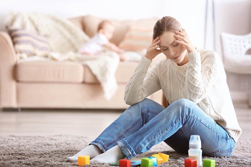 gestresste junge Mutter sitzt mit Spielzeug auf dem Boden, während das Baby auf der Couch liegt