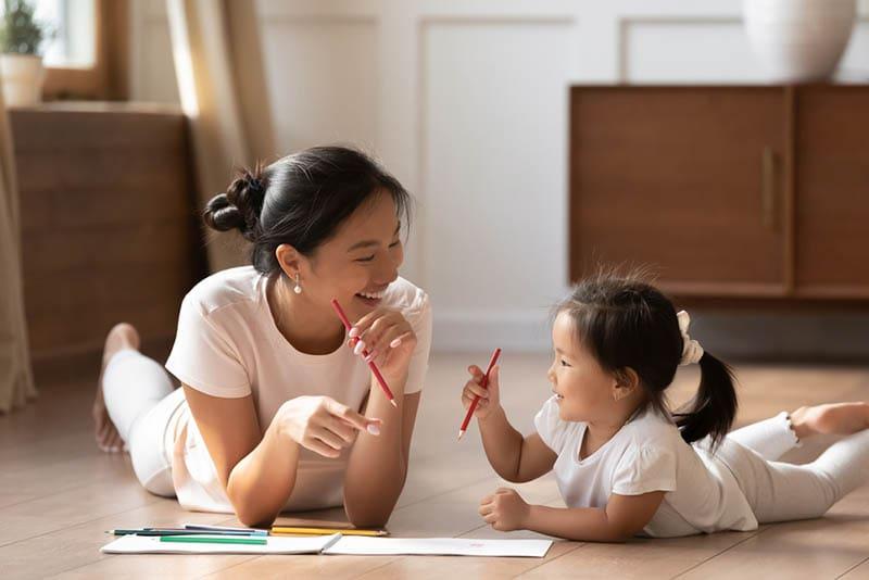 glückliche Mutter, die mit ihrer Tochter auf dem Boden liegt und Stifte hält