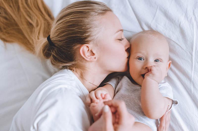 glückliche junge Mutter, die ihren Sohn auf dem Bett küsst