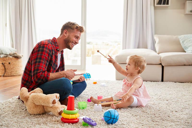 glücklicher junger Vater spielt mit seiner kleinen Tochter auf dem Boden im Wohnzimmer