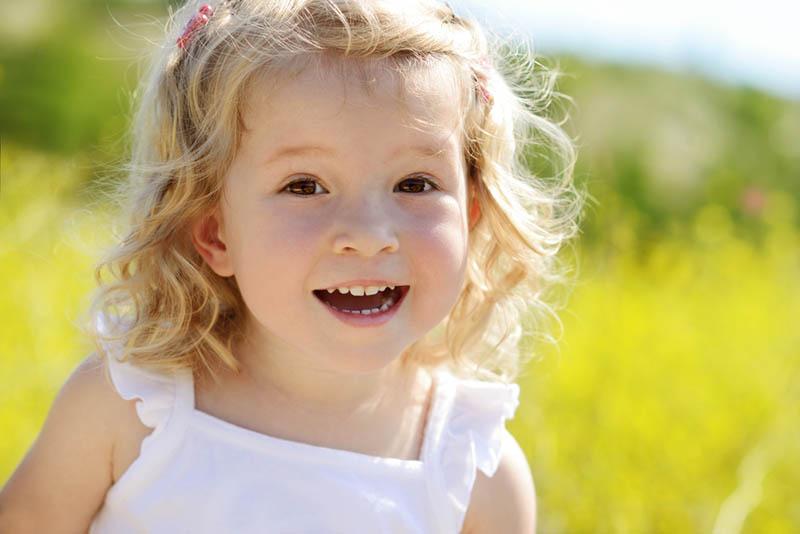 glückliches Kleinkind-Mädchen im Rapsfeld stehend