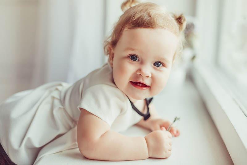 glückliches kleines Mädchen, das auf dem Fenster steht und posiert