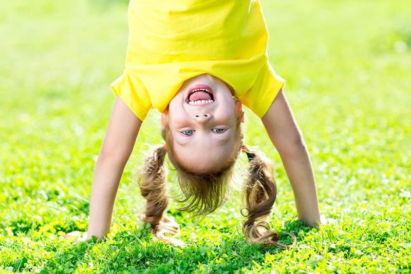 glückliches kleines Mädchen stehend auf Hände im Freien auf dem Gras