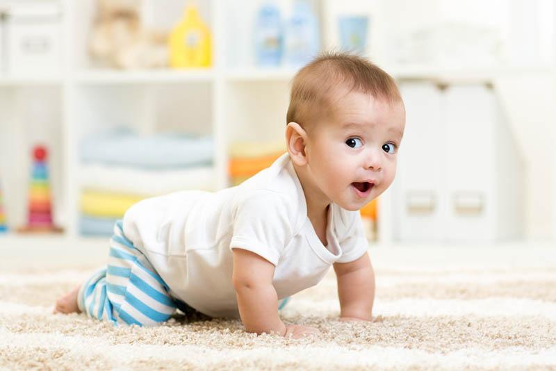interessanter Babyjunge, der zu Hause auf dem Boden krabbelt