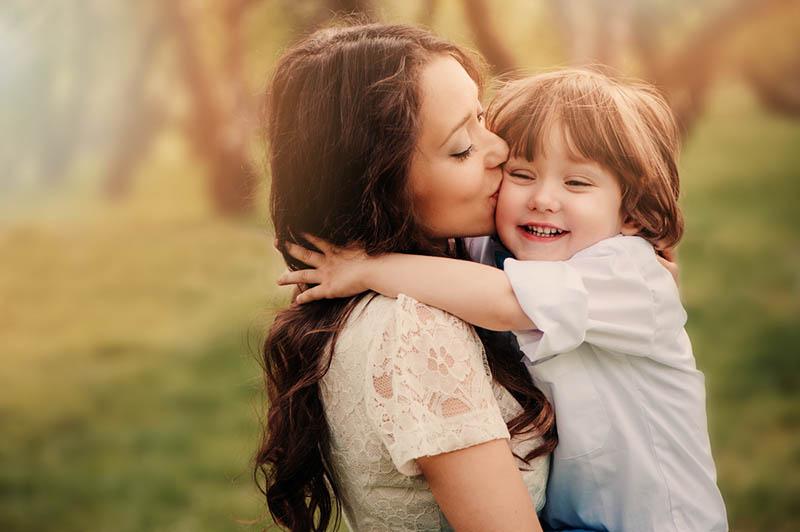 junge Mutter küsst ihren glücklichen Sohn in den Armen im Freien