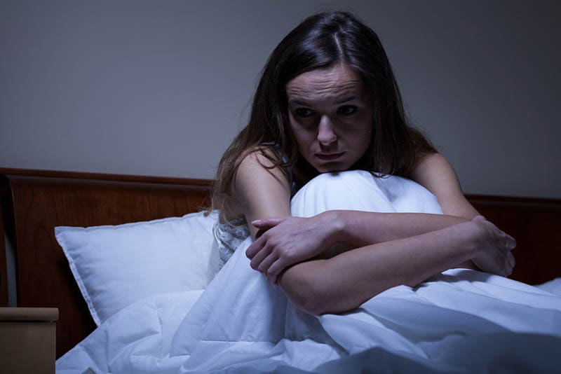 junge besorgte Frau, die nachts in tiefen Gedanken im Bett sitzt