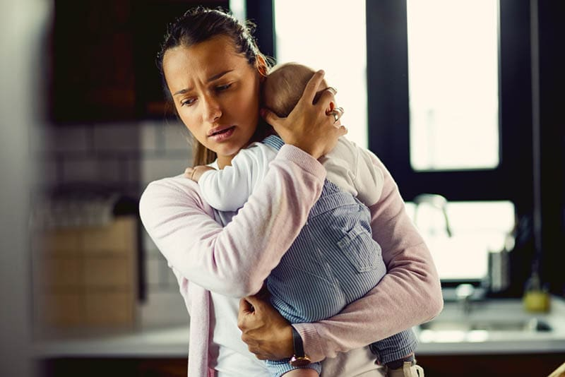 junge besorgte Mutter mit Baby im Arm zu Hause