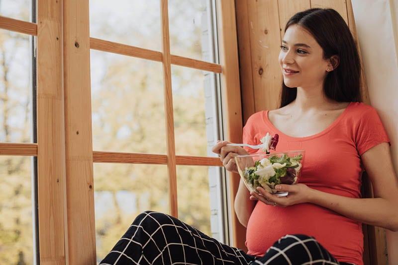 junge schwangere Frau sitzt am Fenster und isst einen Salat