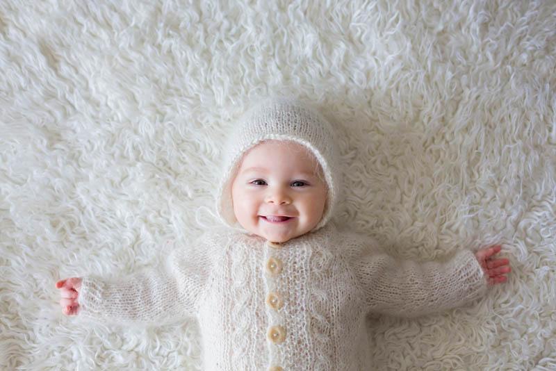 kleiner Baby-Junge in weißen gestrickten Strampler und eine Mütze lächelnd auf dem Bett