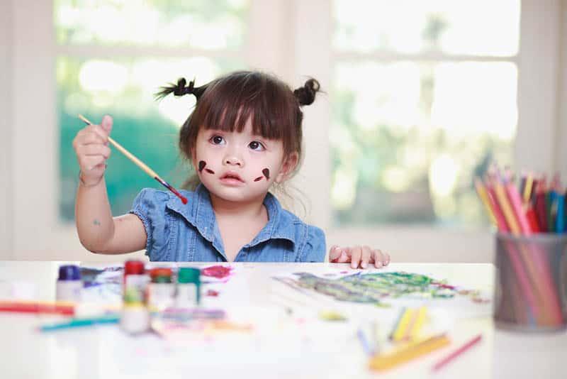 kleines Mädchen hält einen Pinsel und malt am Tisch