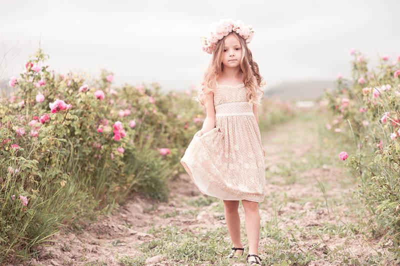 kleines Mädchen in Kleid und Blume Stirnband zu Fuß in der Blume Feld