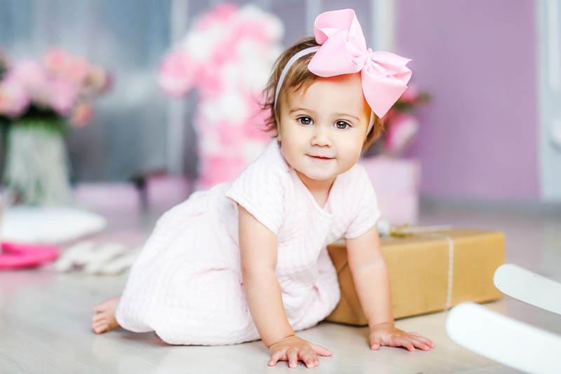 kleines Mädchen mit großen rosa Schleife auf dem Kopf sitzt auf dem Boden mit Geschenk