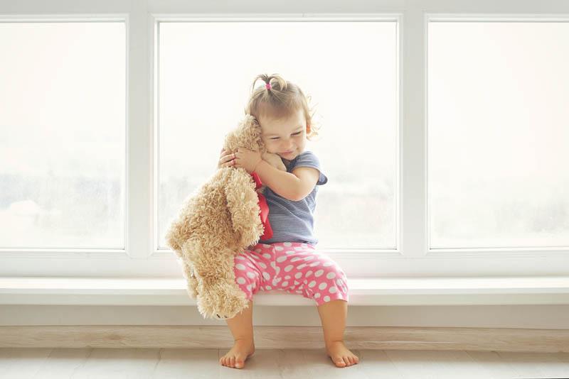 kleines Mädchen umarmt ihren Teddybär Spielzeug durch das Fenster