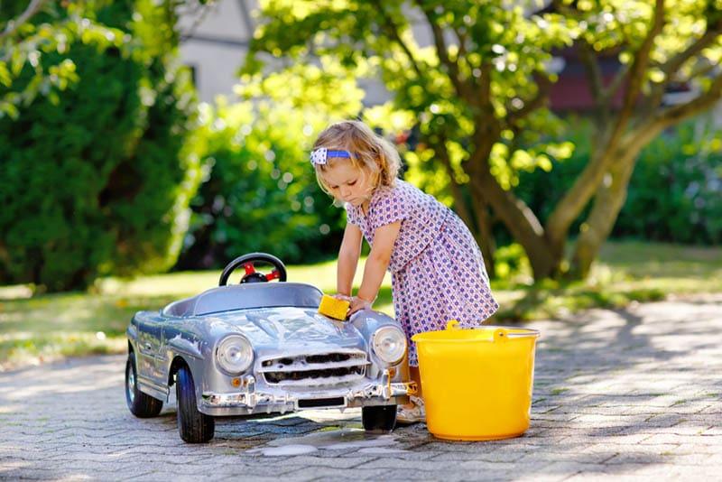 kleines Mädchen wäscht ihr Auto Spielzeug im Freien