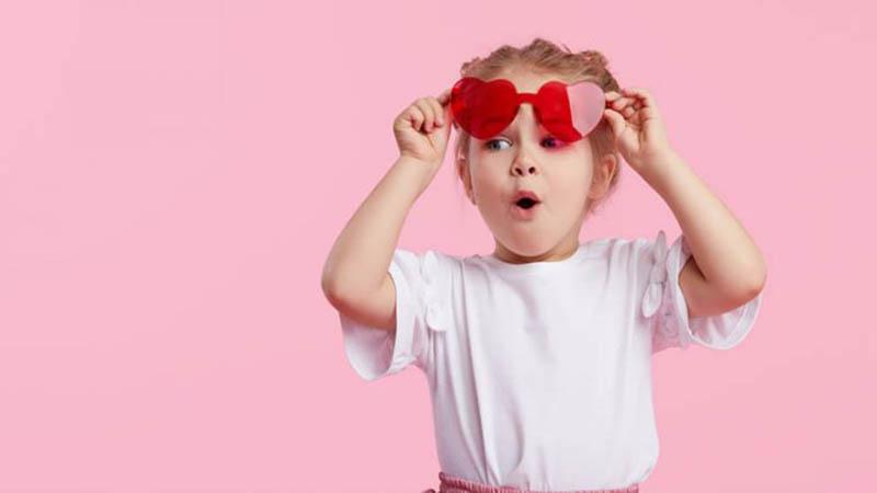 kleines Mädchen zieht rote Sonnenbrille und handeln bewundernd