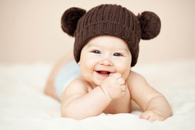 lächelnd Baby Junge trägt braunen Hut und lächelnd auf dem Bett