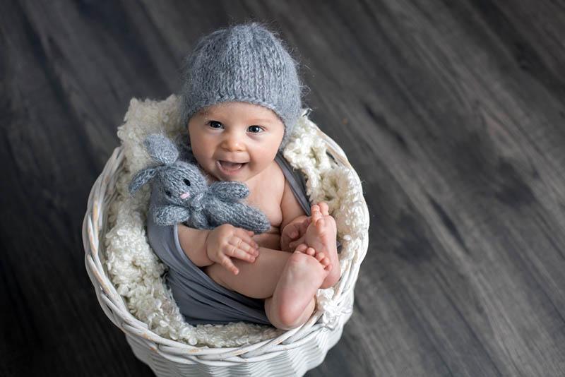 lächelnd Baby posiert in einem Korb mit einem Spielzeug