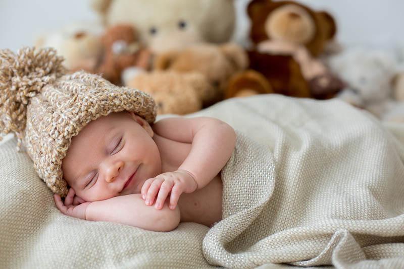 lächelnd Baby schlafen mit Wintermütze auf mit Decke bedeckt