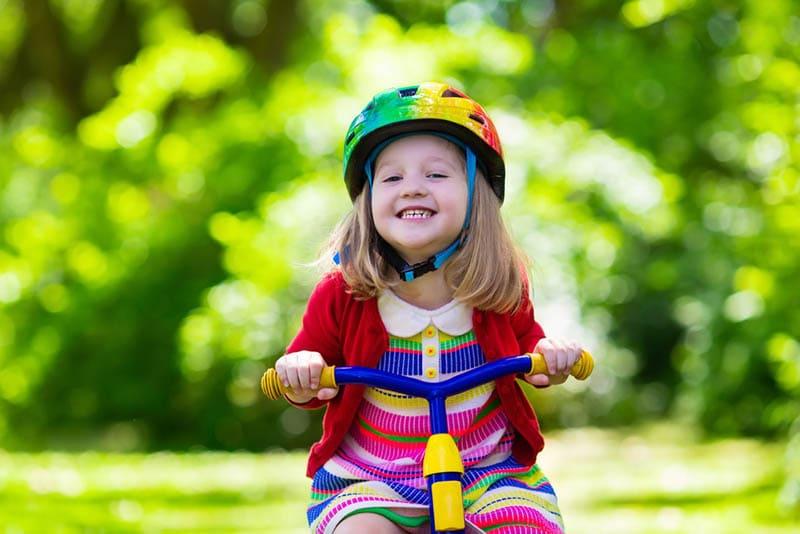 lächelnd kleines Mädchen fahren ein buntes Fahrrad im Freien