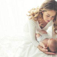 glückliche Mutter hält ihr Baby Sohn auf dem Bett