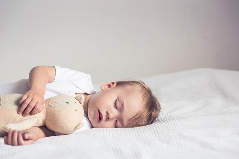 niedlichen Baby Junge schlafen fest auf dem Bett in Umarmung mit Spielzeug