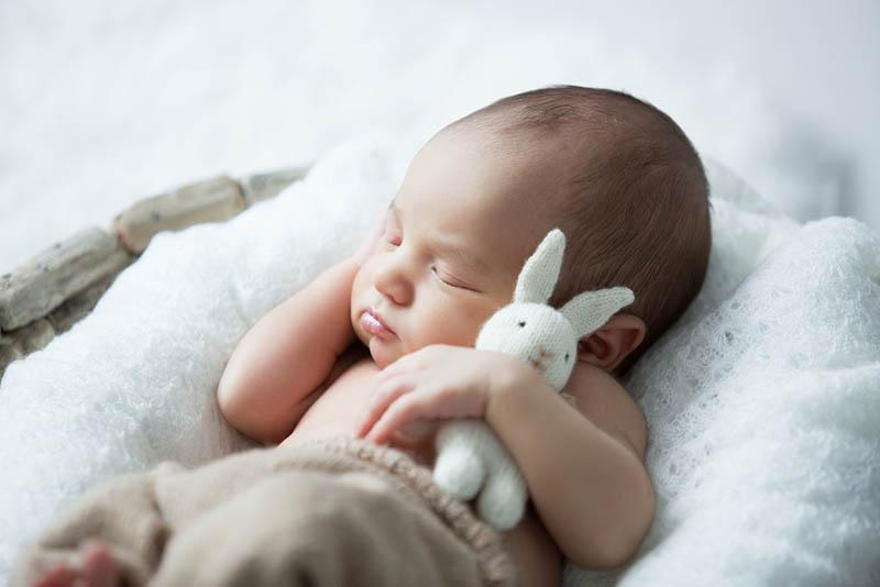 niedlichen Baby Junge schlafen in Umarmung mit Kaninchen Spielzeug
