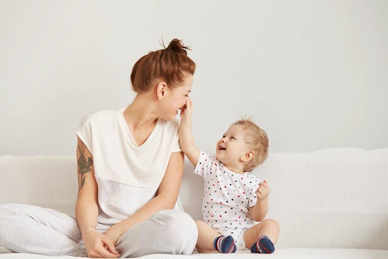 niedlichen Baby Junge sitzt auf der Couch mit seiner Mutter und spielen mit ihr am Morgen