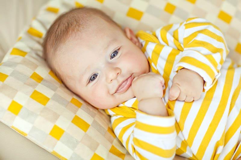 niedlichen Baby-Junge trägt gelben Pijama und liegt auf dem Bett