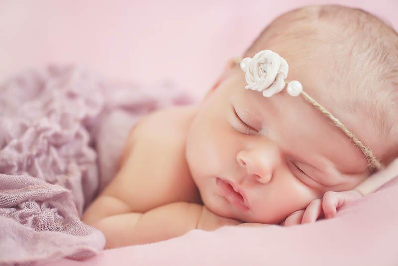 niedlichen Baby Mädchen schlafen mit Blume Stirnband auf dem Kopf