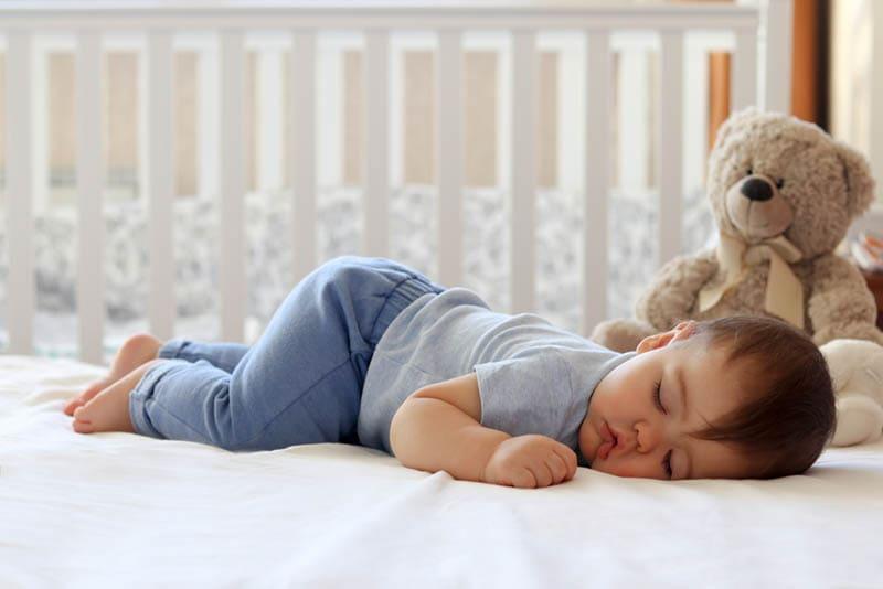 niedlichen Baby schlafen auf dem Bauch auf dem Bett im Schlafzimmer