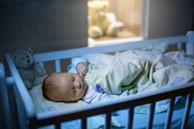 niedlichen Baby schlafen in einer Wiege mit Decke bedeckt in der Nacht im Schlafzimmer