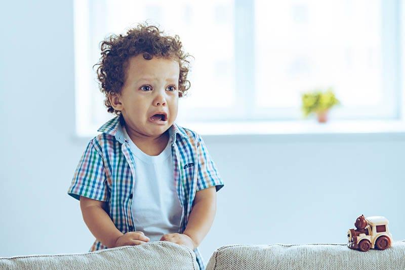 niedlichen kleinen Jungen mit lockigem Haar weinen im Wohnzimmer